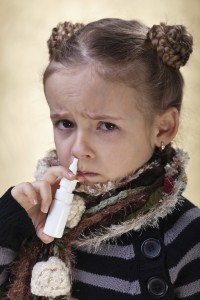 Little girl with the flu using nasal spray